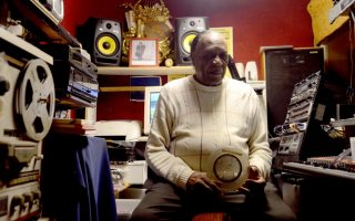 """Charlie McClendon in his home studio with the original reel-to-reel recording of """"Rainy Night in Georgia."""" photo by pat Jarrett."""