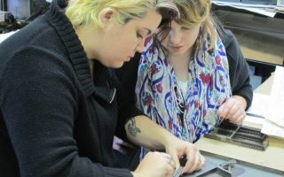 <p>Two Sweet Briar College students, Katie Holloway and Sally Toms, learn to set movable type at the Virginia Arts of the Book Center.</p>